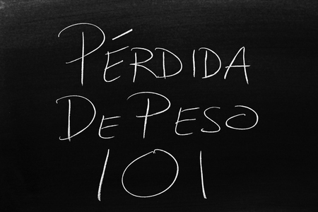 The words Pérdida De Peso 101 on a blackboard in chalk.  Translation: Weight Loss 101