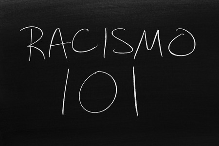 The words Racismo 101 on a blackboard in chalk.  Translation: Racism 101