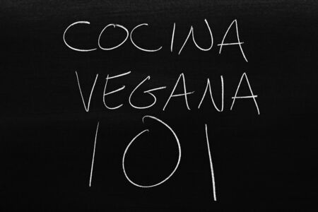 The words Cocina Vegana 101 on a blackboard in chalk.  Translation: Vegan Cooking 101