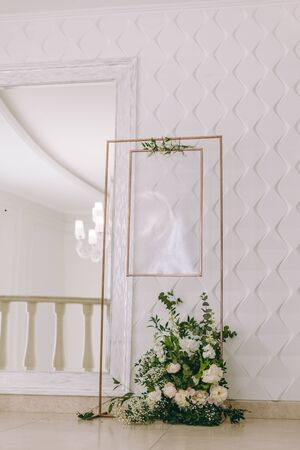 List, plan, chart of the seating area of guests at the tables at restaurant. Tables wedding guests on the easel on wedding reception. The frame is decorated with green flowers and greenery.