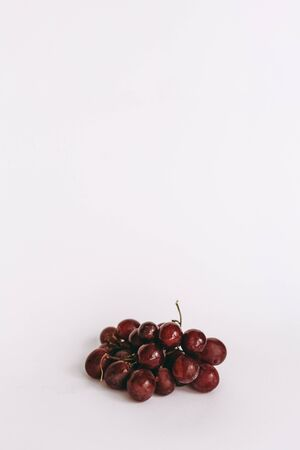Grapes red with drops of water on white background.