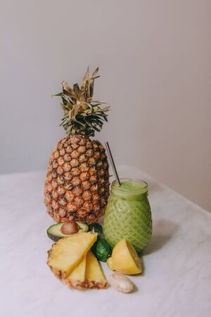 Homemade pineapple smoothie made with lemon, ginger, avocado, cucumber on a white table Imagens