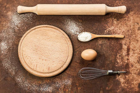 Dishes and ingredients for pizza dough. Eggs, flour, whisk, rolling pin and round board on an old vintage background. Baking concept, copy space. Culinary background.