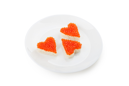 Three sandwiches with red caviar in the shape of heart lie on a white plate isolated on white background.