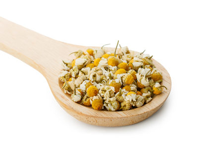 Dried chamomile flowers and wooden spoon isolated on white background Banco de Imagens