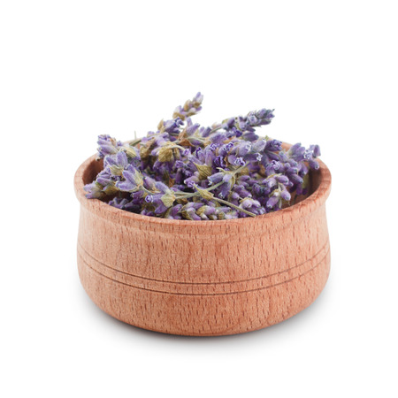 Dried lavender flowers in wooden bawl isolated on white background.