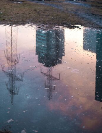Water reflection of power lines and industrial building during winter time with the pink sky