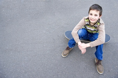 Teenage boy sitting on the skateboard on the pavement Stock Photo - 12988008