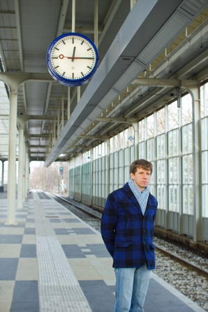 A man waiting for a train under a clock Stock Photo - 13046385