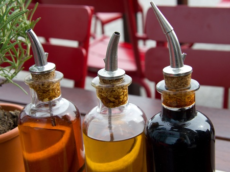 balsamic vinegar bottles and condiments on the table in an open cafe photo