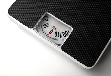 Dieting concept with scales on the white background photo