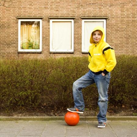 sudadera: Cute adolescente en una sudadera con capucha de color amarillo con una pelota naranja Foto de archivo