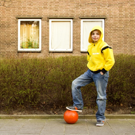 hooded sweatshirt: Cute teenage boy in a yellow hoodie with an orange ball