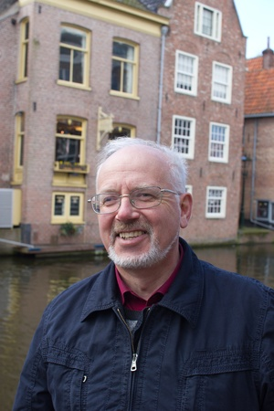 Portrait of the Smiling Old Man With a Grey Beard on Background of Traditional Dutch Town photo