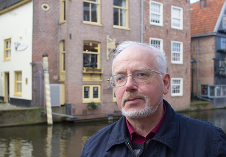 Portrait of the Old Man With a Grey Beard on Background of Traditional Dutch Town photo