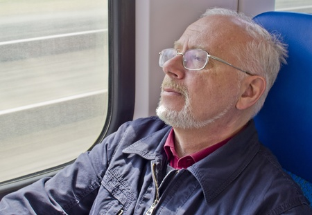 Relaxed old man sitting near the window in the carriage photo