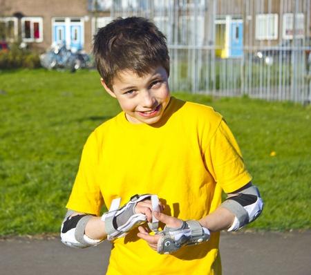 niño sonriente adolescente ajustando su patinar kit de protección