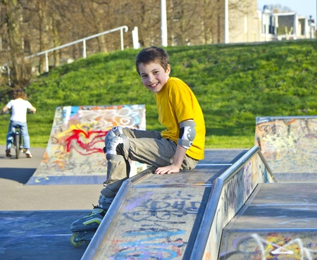 rollerblading: smiling teenage boy in roller-blading protection kit in a skate park Stock Photo