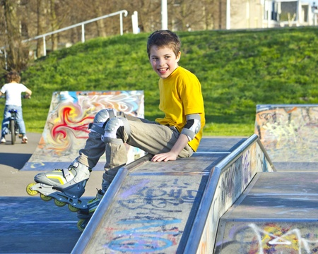 smiling teenage boy in roller-blading protection kit in a skate park photo