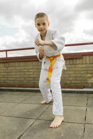 judoka teen boy training judo on the sky background photo