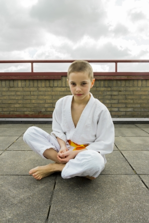 judoka teen boy sitting on the roof  sky background  photo
