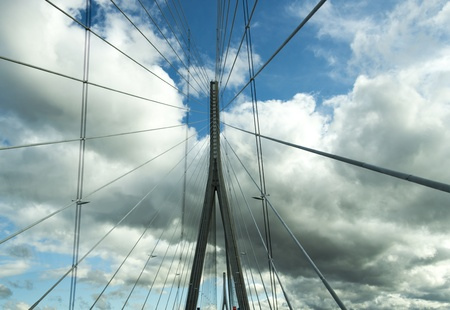 Landmark of modern silver steel bridge against a cloudy blue sky photo
