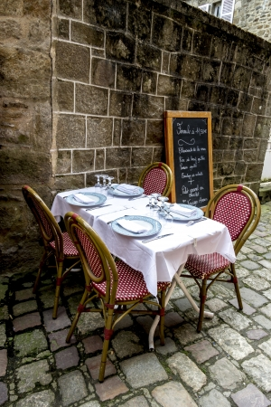 atmosphere: Dining table in front of the french medieval buildings