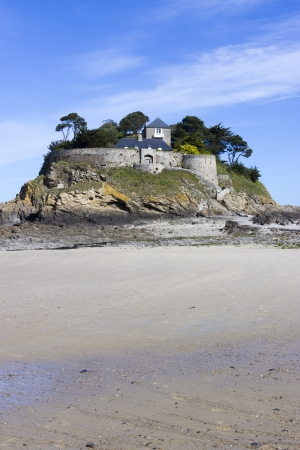 Landscape, seascape with beach and a house on top of a rock. photo