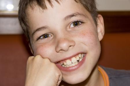 Cute teenage boy smiling (close up portrait)