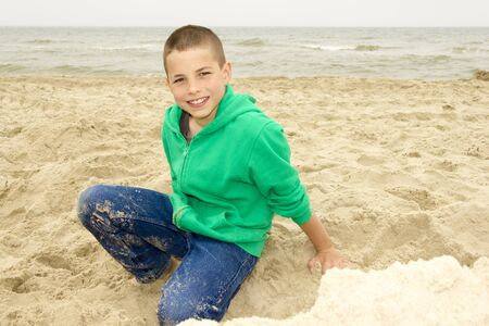 cute boy playing in sand on beach, Northern Sea coast photo