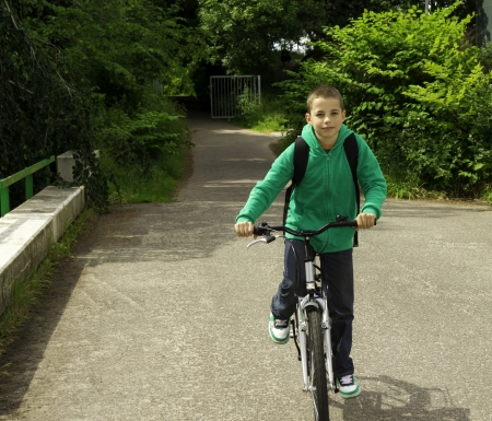 Young school boy with backpack on a bicycle photo