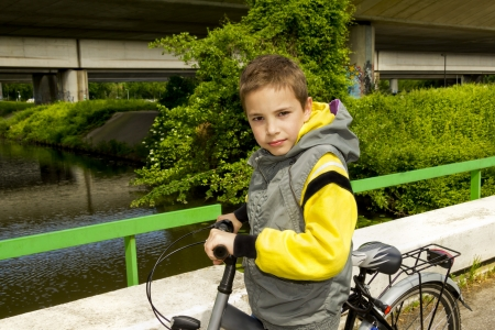 sleeveless hoodie: Young cute school boy with bicycle on the bridge Stock Photo