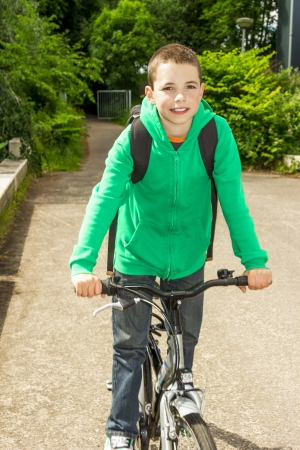 only boys: Young school boy with backpack on a bicycle