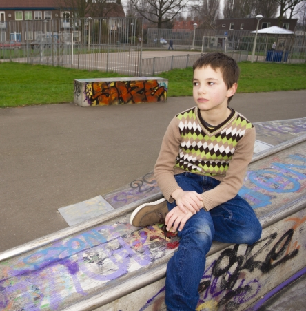 Cute Boy Sitting In Playground photo