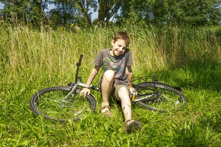 The boy sitting on the bike in grass photo