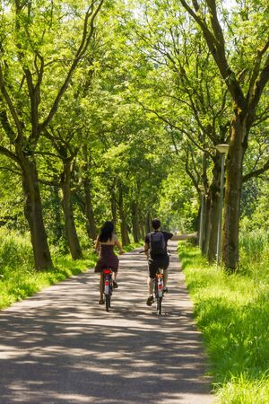 Couple riding bicycle along trees alley photo