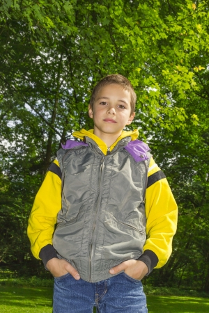 Cute  boy in a yellow hoodie against green tree background photo
