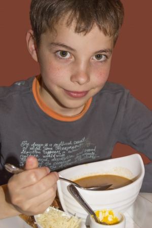 Cute teenage boy eating soup for dinner photo