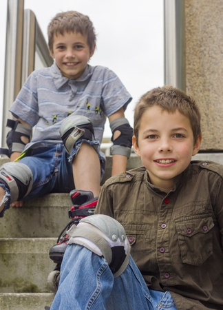 rollerblading: two smiling teenage boys in roller-blading protection kits