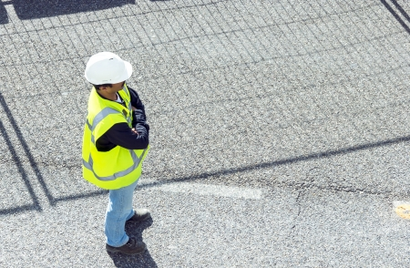 standing worker wearing white overalls and yellow high visibility safety jacket  on road works; horizontal orientation photo
