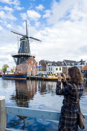 dutch girl: Tourist girl is taking pictures of traditional Dutch windmill