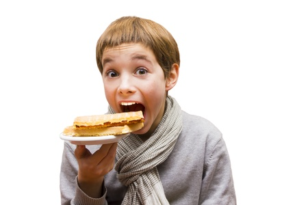 Portrait of a cute boy eating a waffle - isolated on white photo