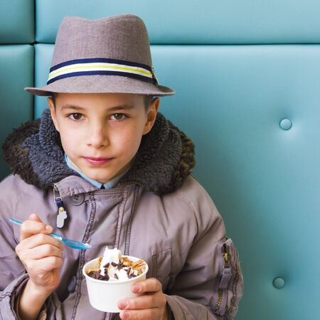 Cute teenage boy eating ice cream with chocolate topping photo