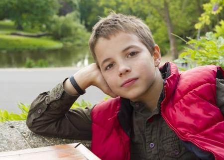arrogant teen: Cute thoughtful teenage boy against green background