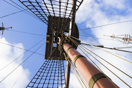Marine rope ladder, mast and ropes of a classic sailboat against blue sky. photo