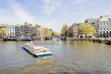 View on the houseboats with cruiseboat in Amsterdam the Netherlands