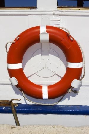 floatable: Orange ring buoy hanging on white painted boat