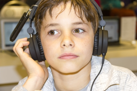Portrait of a sweet young boy listening to music on headphones photo