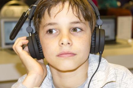 Portret van een lieve jonge jongen luisteren naar muziek op de koptelefoon
