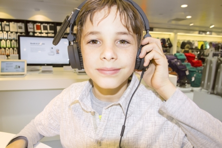 Portrait of a sweet young boy listening to music on headphones Stock Photo - 21410196